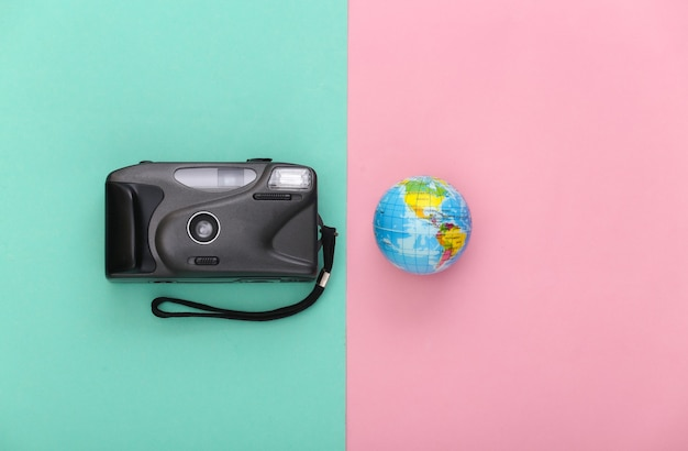 Reisconcept. camera met een wereldbol op een blauw-roze achtergrond. bovenaanzicht