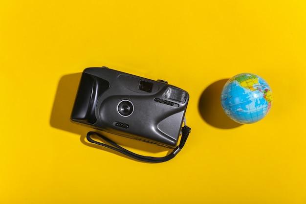 Reisconcept. camera met een wereldbol op gele achtergrond met schaduw. bovenaanzicht