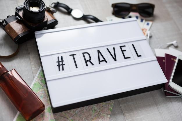 Reisconcept close-up van reisobjecten en lichtbak met hashtag reizen