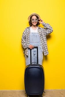 Reisconcept. gelukkige toeristenvrouw die hoed en zonnebril draagt klaar voor reis met geïsoleerde koffer en paspoort.
