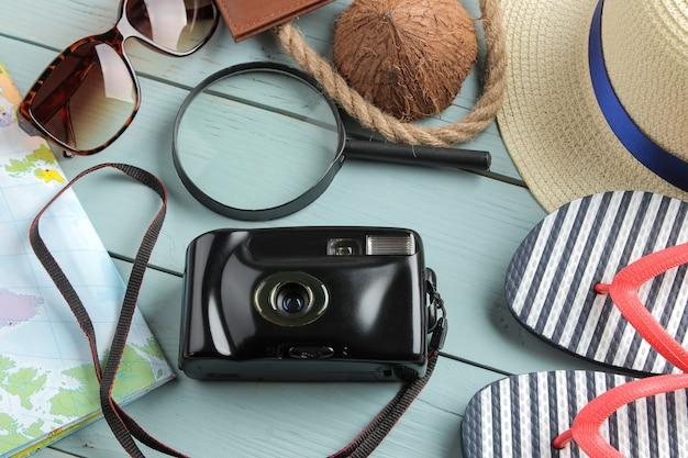 Reisconcept hoed, camera, paspoort, kaart en zonnebril op een houten blauwe tafel.