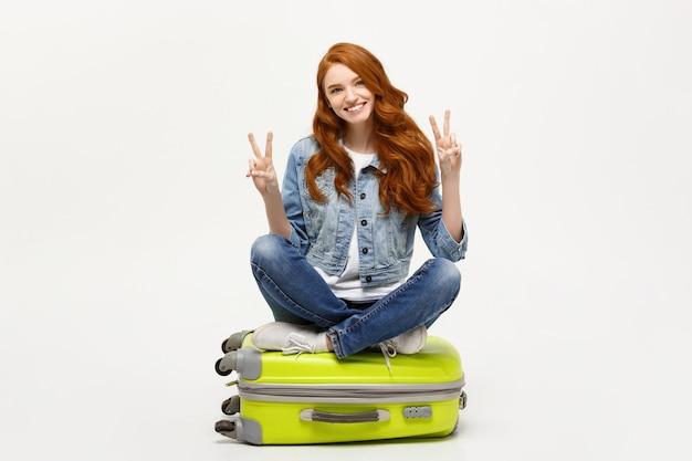 Reisconcept: jonge glimlachende kaukasische vrouw die op koffer situeert die twee vingers toont. geïsoleerd op witte achtergrond.