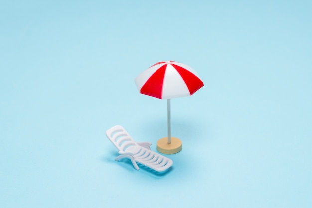 Reisconcept. ligstoel, rode paraplu op een blauwe achtergrond. ruimte kopiëren.