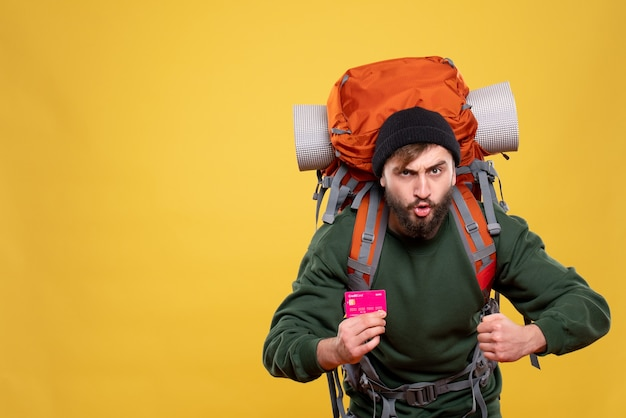 Reisconcept met ambitieuze jonge kerel met packpack en bankkaart op geel te houden