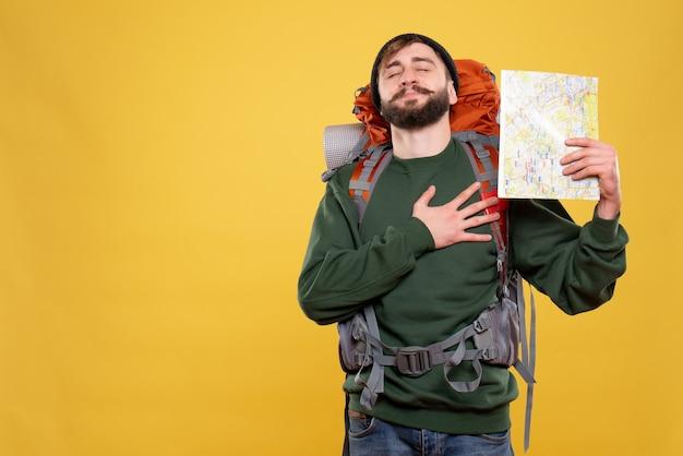 Reisconcept met dromerige jonge kerel met packpack en kaart vasthouden hand op zijn hart op geel