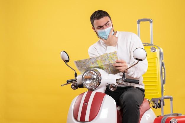 Reisconcept met een denkende man met een medisch masker die op een motorfiets zit met een gele koffer erop en een kaart op geel toont