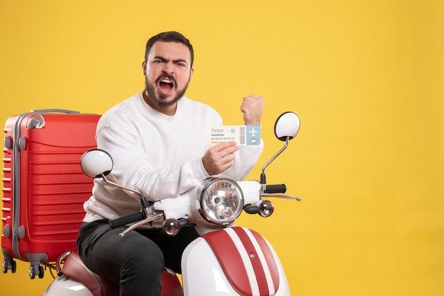 Reisconcept met een emotionele ambitieuze man die op een motorfiets zit met een koffer erop met een kaartje op geel
