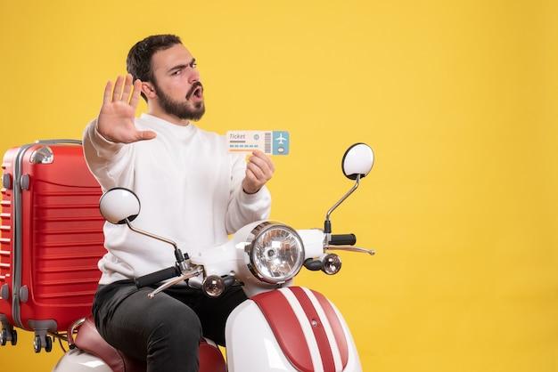 Reisconcept met een jonge emotionele man die op een motorfiets zit met een koffer erop en een kaartje op geel toont
