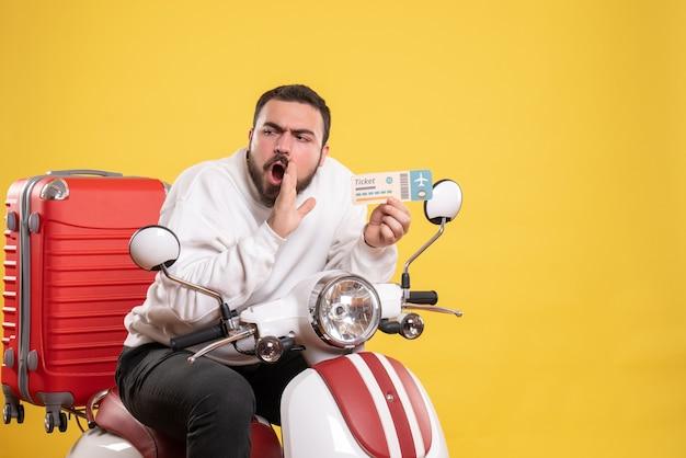 Reisconcept met een jonge emotionele man die op een motorfiets zit met een koffer erop en iemand op geel roept