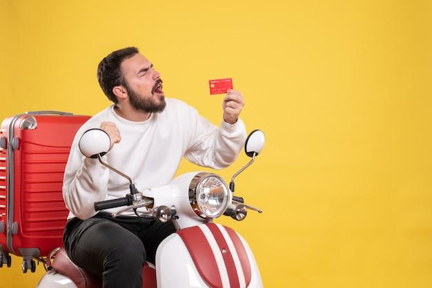 Reisconcept met een jonge, gelukkige en emotionele reizende man die op een motorfiets zit met een koffer erop met een bankkaart op geel