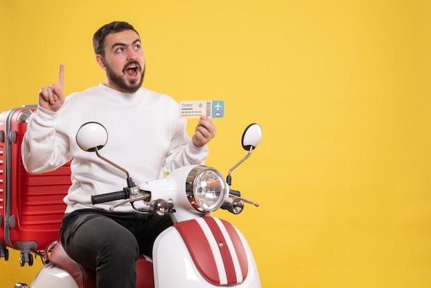 Reisconcept met een jonge, gelukkige reizende man die op een motorfiets zit met een koffer erop die een bankkaart toont en naar boven wijst op geel