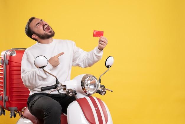 Reisconcept met een jonge, gelukkige reizende man die op een motorfiets zit met een koffer erop en een bankkaart op geel wijst