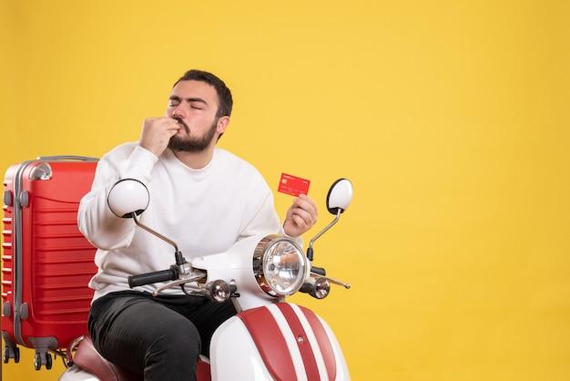 Reisconcept met een jonge, gelukkige reizende man die op een motorfiets zit met een koffer erop met een bankkaart die een perfect gebaar maakt op geel