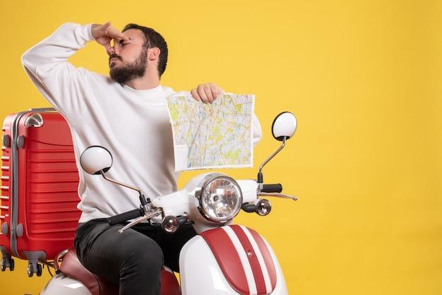 Reisconcept met een jonge kerel die op een motorfiets zit met een koffer die een stankgebaar maakt op geel?