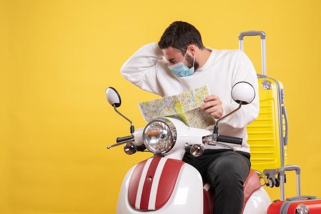 Reisconcept met een jonge kerel met een medisch masker die op een motorfiets zit met een gele koffer erop en een kaart vasthoudt die lijdt aan hoofdpijn
