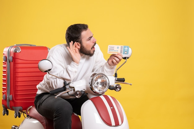 Reisconcept met een jonge man die op een motorfiets zit met een koffer erop die een kaartje laat zien en de laatste roddels op geel luistert