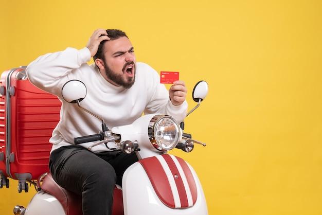 Reisconcept met een jonge verwarde reizende man die op een motorfiets zit met een koffer erop met een bankkaart op geel