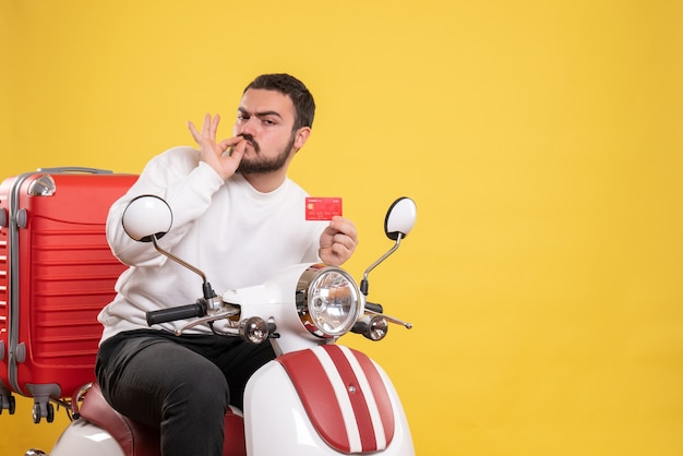 Reisconcept met een jonge zelfverzekerde reizende man die op een motorfiets zit met een koffer erop met een bankkaart die een perfect gebaar maakt op geel