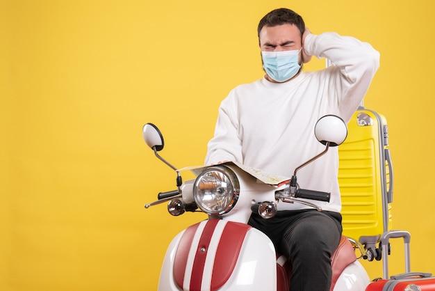 Reisconcept met een nerveuze man met een medisch masker die op een motorfiets zit met een gele koffer erop en een kaart vasthoudt die aan hoofdpijn lijdt