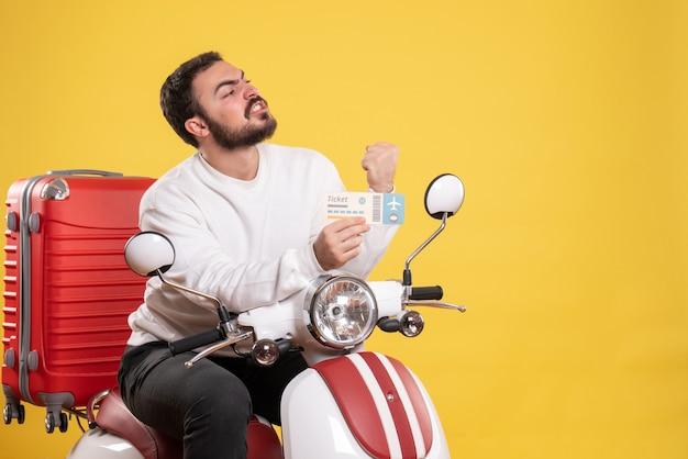Reisconcept met een trotse ambitieuze man die op een motorfiets zit met een koffer erop met een kaartje op geel
