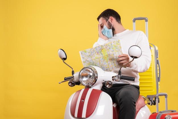Reisconcept met een verwarde man met een medisch masker die op een motorfiets zit met een gele koffer erop en een kaart vasthoudt die aan hoofdpijn lijdt