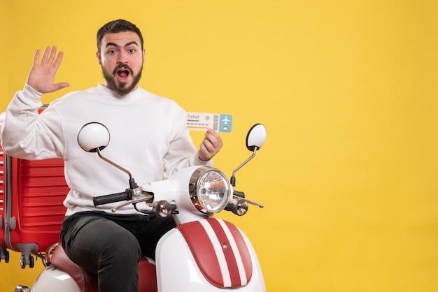 Reisconcept met emotionele man zittend op motorfiets met koffer erop met ticket op geel