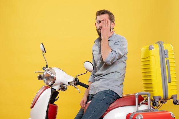 Reisconcept met emotionele nerveuze jongeman zittend op moto met koffers erop op geel