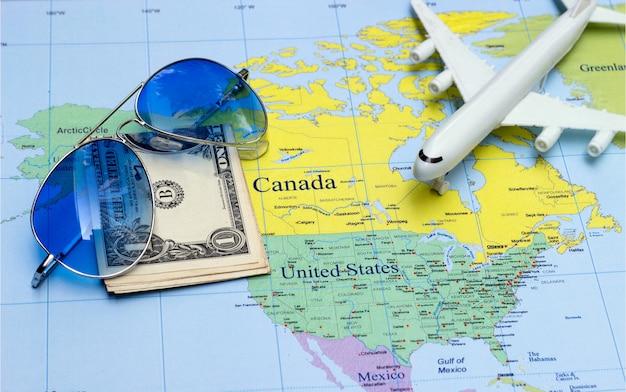 Reisconcept met geld, vliegtuig en zonnebril