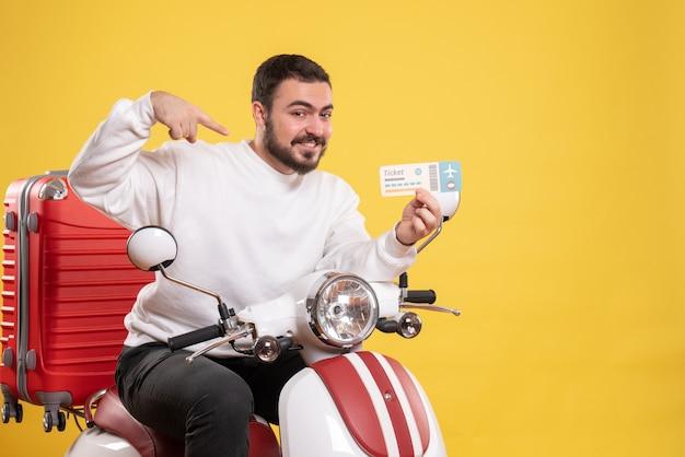 Reisconcept met gelukkig lachende man zittend op motorfiets met koffer erop met ticket op geel showing