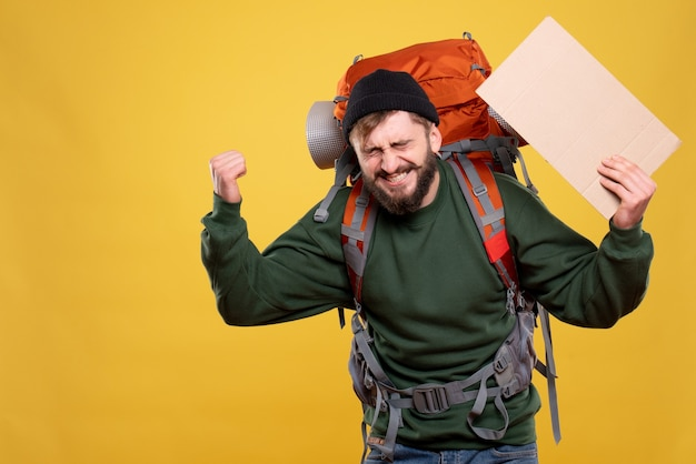 Reisconcept met gelukkige emotionele jongeman met packpack en een blad vasthouden zonder erop op geel te schrijven