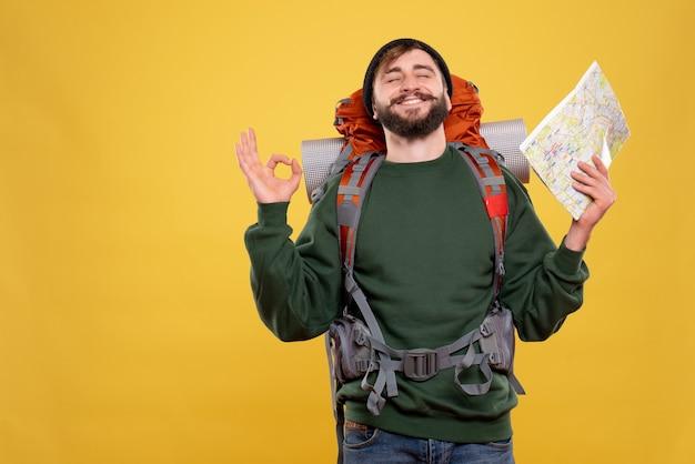 Reisconcept met glimlachende jonge kerel met packpack en kaart die op geel droomt te houden
