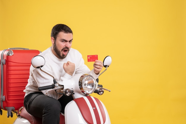 Reisconcept met jonge ambitieuze emotionele reizende man die op een motorfiets zit met een koffer erop met een bankkaart op geel