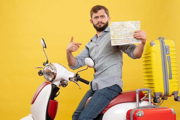 Reisconcept met jonge emotionele bebaarde man zittend op een motorfiets en wijst naar voren wijzende kaart erop op geel