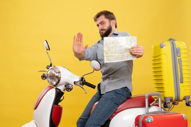 Reisconcept met jonge emotionele bebaarde man zittend op motocycle en naar voren wijzend bedrijf kaart met vijf erop op geel