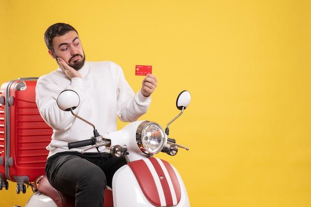 Reisconcept met jonge geconcentreerde reizende man zittend op motorfiets met koffer erop met bankkaart op geel