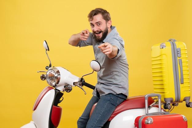 Reisconcept met jonge lachende bebaarde man zittend op motocycle en erop vooruit gericht op geel