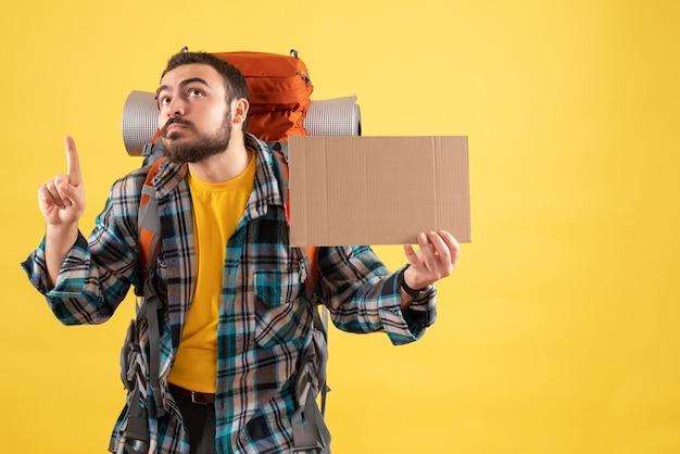 Reisconcept met jonge reizende man met rugzak die een laken vasthoudt zonder te schrijven en omhoog wijst op geel