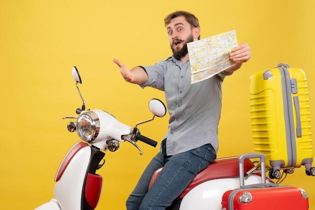 Reisconcept met jonge verrast emotionele bebaarde man zittend op de motorfiets en naar voren gericht houden kaart erop op geel