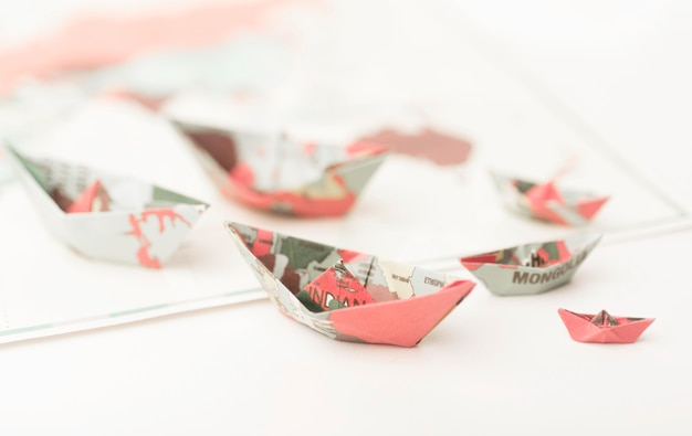 Reisconcept met kleine papieren bootjes