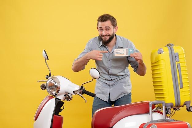 Reisconcept met lachende jonge man achter motocycle met koffers erop en kaartje op geel te houden
