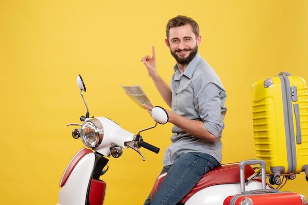 Reisconcept met lachende jonge man zittend op moto met koffers erop en kaart op geel te houden