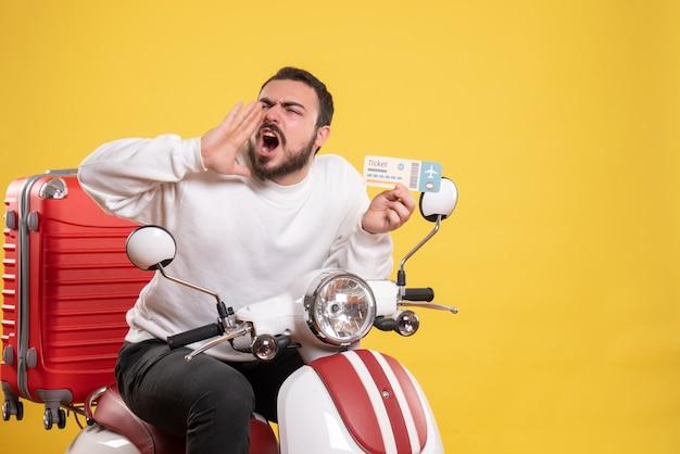 Reisconcept met nerveuze man zittend op motorfiets met koffer erop die iemand op geel roept someone