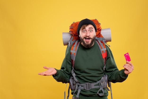 Reisconcept met nieuwsgierige jonge kerel met packpack en bankkaart op geel te houden