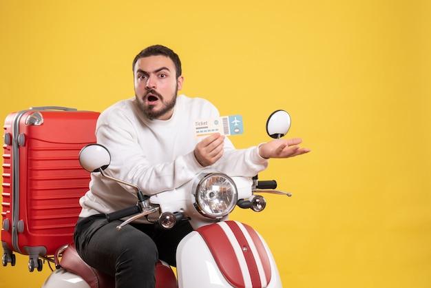 Reisconcept met nieuwsgierige man zittend op motorfiets met koffer erop met ticket op geel