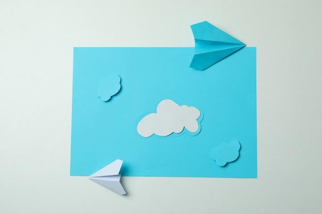 Reisconcept met papieren vliegtuigen en wolken