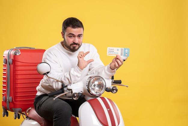 Reisconcept met tevreden man zittend op motorfiets met koffer erop met ticket op geel