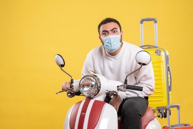 Reisconcept met verraste man met medisch masker zittend op motorfiets met gele koffer erop op geel