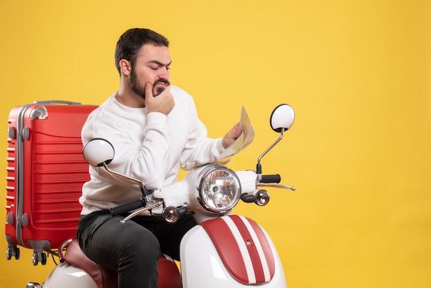 Reisconcept met verwarde man zittend op motorfiets met koffer erop met kaart op geel