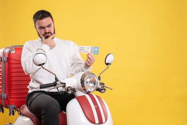 Reisconcept met verwarde man zittend op motorfiets met koffer erop met ticket op geel