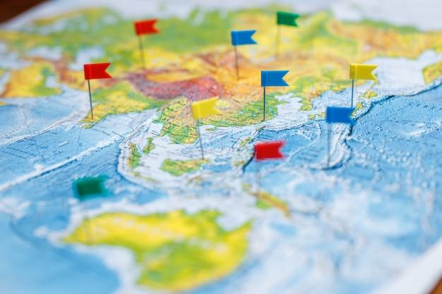 Reisconcept met vlagpunaisen en wereldkaart.